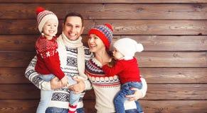 愉快的家庭母亲、父亲和孩子冬天帽子的在woode 免版税库存图片