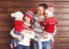愉快的家庭母亲、父亲和孩子冬天帽子的在woode 免版税库存照片