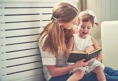 愉快的家庭母亲儿童小女孩阅读书 免版税库存图片