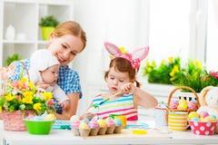愉快的家庭母亲和两个孩子为复活节做准备,油漆 库存图片