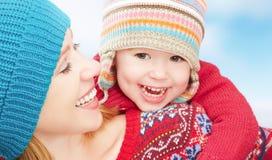 愉快的家庭母亲和使用在冬天的婴孩小女儿 免版税库存图片