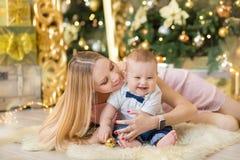 愉快的家庭母亲和使用在家圣诞节假日的婴孩小儿子 有妈妈的小孩在有C的欢乐地装饰的屋子 库存图片