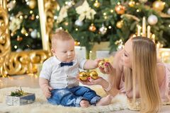 愉快的家庭母亲和使用在家圣诞节假日的婴孩小儿子 有妈妈的小孩在有C的欢乐地装饰的屋子 免版税库存照片