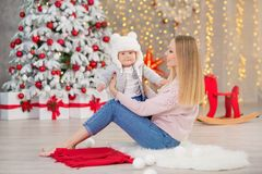 愉快的家庭母亲和使用在家圣诞节假日的婴孩小儿子 有妈妈的小孩在有C的欢乐地装饰的屋子 库存照片