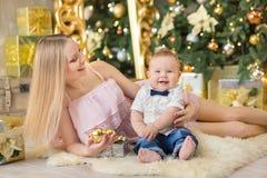 愉快的家庭母亲和使用在家圣诞节假日的婴孩小儿子 有妈妈的小孩在有C的欢乐地装饰的屋子 免版税库存图片