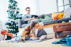 愉快的家庭母亲和使用在家圣诞节假日的婴孩小儿子 免版税库存图片
