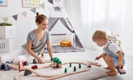愉快的家庭母亲和使用在pl的玩具铁路的儿童儿子 免版税库存照片