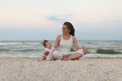 愉快的家庭母亲和做瑜伽的儿童女儿,在海滩的莲花坐思考在日落 免版税库存图片