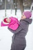愉快的家庭母亲和儿童女儿在一个冬天 免版税图库摄影