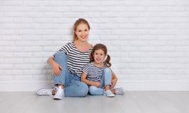 愉快的家庭母亲和儿童女儿在空的墙壁附近 图库摄影