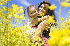 愉快的家庭母亲和儿童女儿获得在黄色花的乐趣 免版税图库摄影