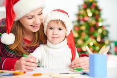愉快的家庭母亲和儿童女儿给圣诞老人o写aletter 库存照片