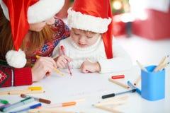 愉快的家庭母亲和儿童女儿给圣诞老人o写aletter 免版税库存图片