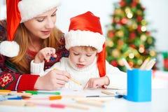 愉快的家庭母亲和儿童女儿给圣诞老人o写aletter 图库摄影