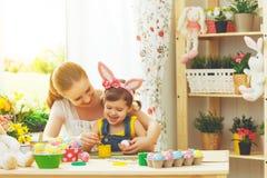 愉快的家庭母亲和儿童女孩绘复活节的鸡蛋 库存照片