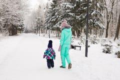 愉快的家庭母亲和儿童小女儿在一个冬天在森林走 免版税库存图片