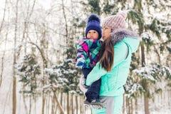 愉快的家庭母亲和儿童小女儿在一个冬天在森林走 库存照片
