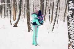 愉快的家庭母亲和儿童小女儿在一个冬天在森林走 库存图片