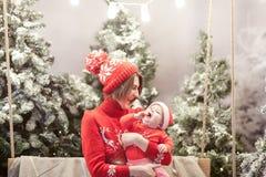 愉快的家庭母亲和儿童男孩圣诞老人帽子的在积雪的圣诞树附近与坐摇摆 明亮的诗歌选 免版税库存照片