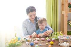 愉快的家庭母亲和儿童男孩在家绘复活节的鸡蛋 庆祝复活节系列 免版税库存照片