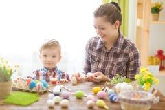 愉快的家庭母亲和儿童男孩在家绘复活节的鸡蛋 庆祝复活节系列 免版税库存图片