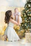 愉快的家庭母亲和儿童男婴在树与礼物,家庭装饰,内部房子的圣诞节早晨 免版税图库摄影