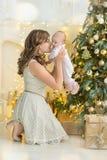 愉快的家庭母亲和儿童男婴在树与礼物,家庭装饰,内部房子的圣诞节早晨 库存照片