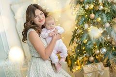 愉快的家庭母亲和儿童男婴在树与礼物,家庭装饰,内部房子的圣诞节早晨 免版税库存图片