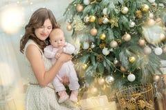 愉快的家庭母亲和儿童男婴在树与礼物,家庭装饰,内部房子的圣诞节早晨 免版税库存照片