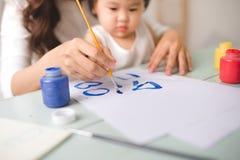 愉快的家庭母亲和女儿一起绘 亚洲妇女恶劣环境测井 图库摄影