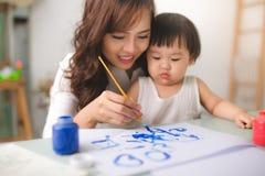 愉快的家庭母亲和女儿一起绘 亚洲妇女恶劣环境测井 免版税库存照片