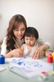 愉快的家庭母亲和女儿一起绘 亚洲妇女恶劣环境测井 库存照片