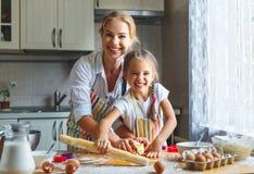 愉快的家庭母亲和女儿在厨房里烘烤揉的面团 库存照片