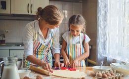 愉快的家庭母亲和女儿在厨房里烘烤揉的面团 库存图片