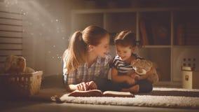 愉快的家庭母亲和女儿在晚上读了一本书 免版税库存图片
