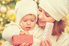 愉快的家庭母亲和女儿帽子的有圣诞节礼物的在冬天 免版税图库摄影
