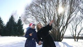 愉快的家庭母亲和女婴女儿奔跑,使用在冬天的步行户外在雪 股票录像