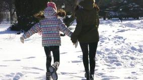 愉快的家庭母亲和女婴女儿奔跑,使用在冬天的步行户外在雪 影视素材