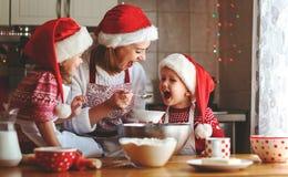 愉快的家庭母亲和孩子烘烤圣诞节的曲奇饼 库存图片