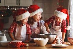 愉快的家庭母亲和孩子烘烤圣诞节的曲奇饼 免版税库存图片
