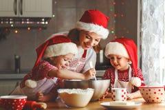 愉快的家庭母亲和孩子烘烤圣诞节的曲奇饼 免版税库存照片