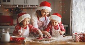 愉快的家庭母亲和孩子烘烤圣诞节的曲奇饼 库存照片