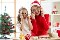 愉快的家庭母亲和孩子获得准备面团的一个乐趣 妇女和女儿烘烤在节日的圣诞节曲奇饼 库存图片