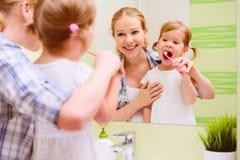 愉快的家庭母亲和掠过她的牙toothb的女儿孩子 免版税库存图片