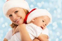 愉快的家庭母亲和婴孩圣诞节帽子的 免版税库存图片
