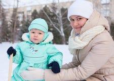 愉快的家庭母亲和婴孩在公园在冬天 免版税图库摄影
