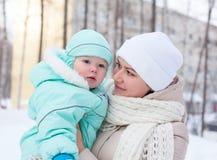 愉快的家庭母亲和婴孩在公园在冬天 免版税库存图片