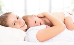 愉快的家庭母亲和婴孩在床上 图库摄影