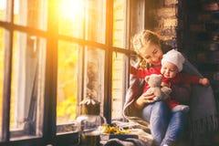 愉快的家庭母亲和婴孩在秋天窗口里 免版税库存图片