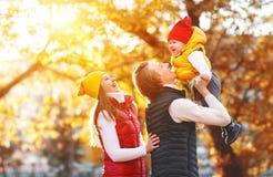 愉快的家庭母亲父亲和婴孩秋天在公园走 库存图片
